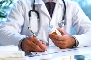 doctor writing prescription for painkiller